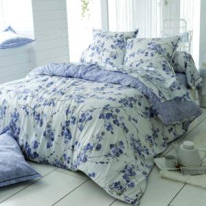 Une housse de couette imprimée de petites fleurs printanières dans des tons de bleus sur fond blanc
