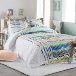 Une house de couette 100% coton imprimée de rayures graphiques, nuances de bleu et de vert sur fond blanc
